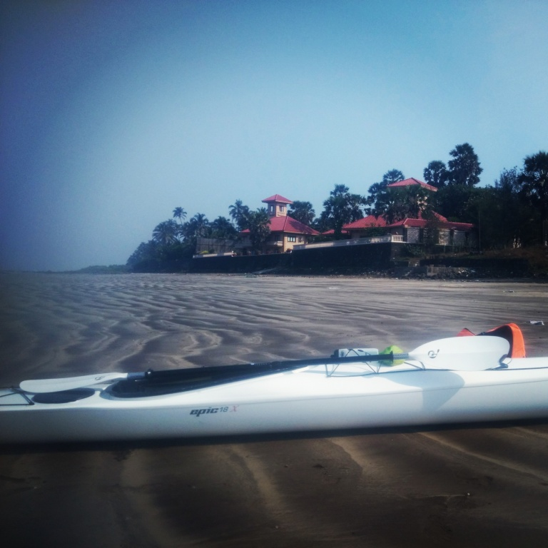 Kayak against someone's sprawling house on the beach